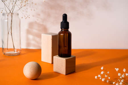 Brown serum or oil glass mock up bottle with pipette over orange background with dried flower and wooden forms side view. Concept of natural organic cosmetic, cosmetology, dermatology. Stockfoto