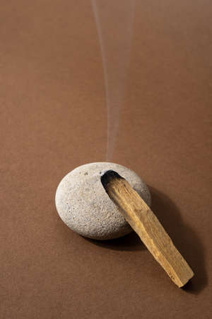 Clearing negative energy and restoring tranquility and calm emotions with Palo Santo.Wood stick on stone vertical shot