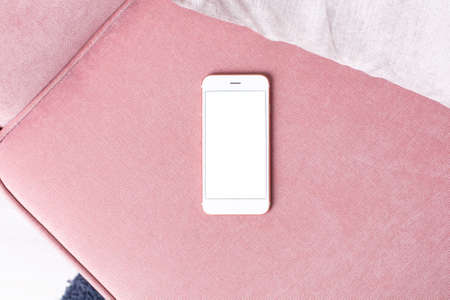 Mobile phone mock up with white screen on pink chair in modern interior