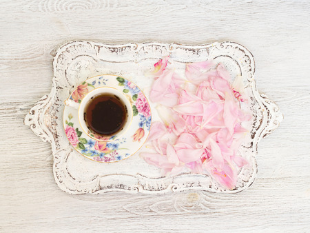 Tea cup with peony petals photo
