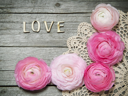 Ranunculus flowers and letters LOVE on wood Archivio Fotografico