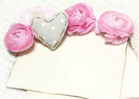 Ranunculus flowers, paper and heart background Archivio Fotografico