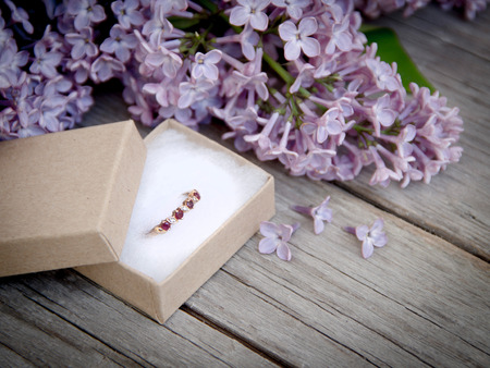 Ring in gift box and lilac on wood photo