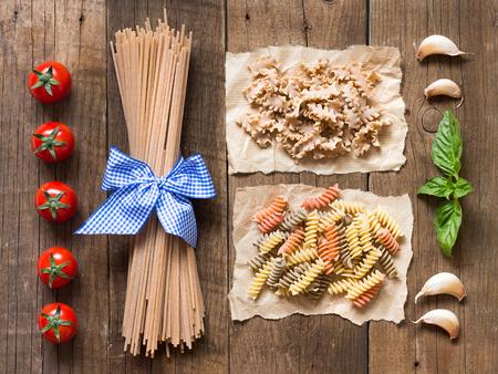 durum: Pasta, tomatoes, garlic and basil on wooden background Stock Photo