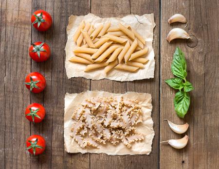 Pasta, pomodori, aglio e basilico sopra il tavolo di legno Archivio Fotografico - 30485748