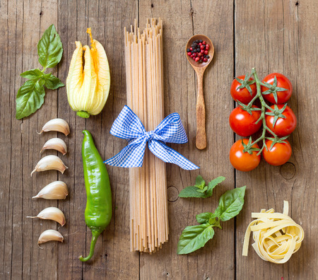 Pasta, vegetables and herbs on wood
