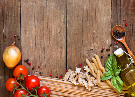 retro dark: Pasta, tomatoes, onion, olive oil and basil on wooden background