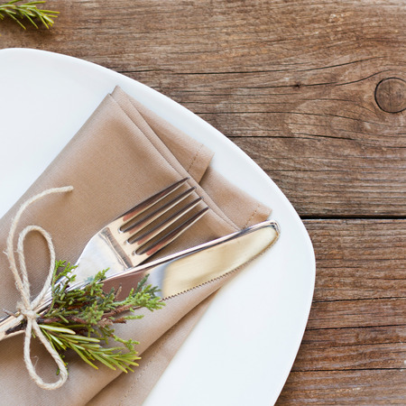 Rustic Table setting with juniper and rosemary decor on old wooden table photo
