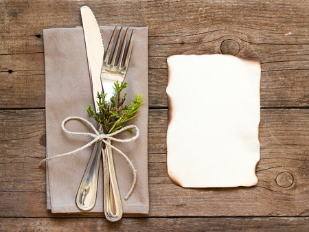 Rustic Table setting and old burned paper on old wooden table photo