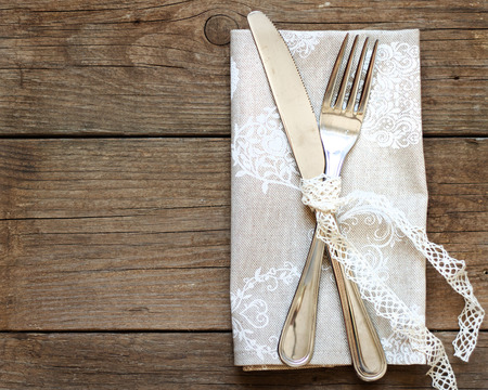 Rustic Table setting with vintage lace ribbon on old wooden table