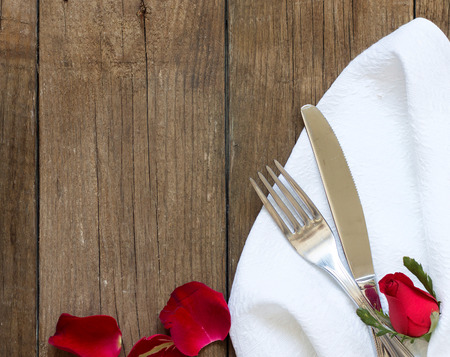 Table setting with rose petals  on old wooden table photo