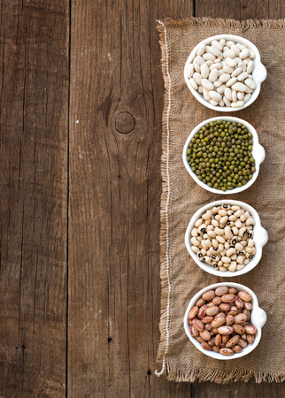lima bean: Assortment of legumes in bowls on wooden table
