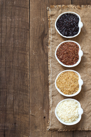 unpolished: Black, red wild rice, basmati and unpolished whole rice in bowls on wooden table Stock Photo