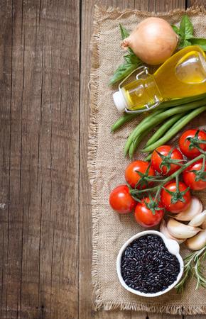 tomate cherry: Arroz org�nico Negro, verduras y hierbas en el fondo de madera Foto de archivo