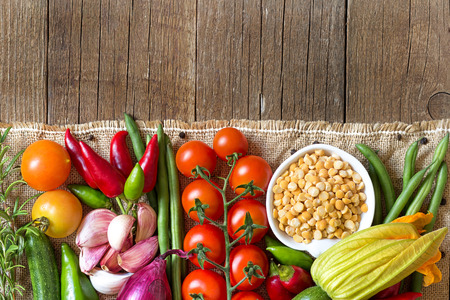 Raw Organic  yellow peas in bowl and vegetables photo