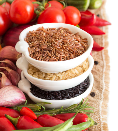 durum: Red, black and unpolished organic rice in bowls and vegetables