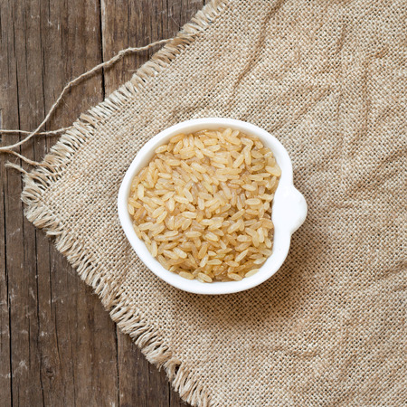 unpolished: Raw unpolished rice in a bowl on burlap