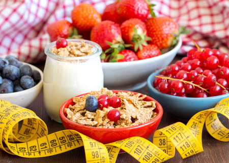Jars of fresh natural yogurt, berries, muesli and measuring tape  photo