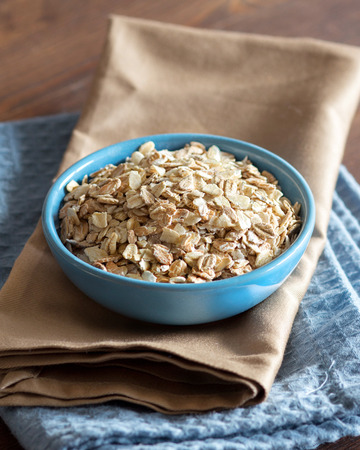 Uncooked rolled oats in a blue bowl on a napkin photo