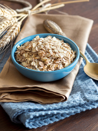 rolled oats: Rolled oats in a blue bowl on a napkin with spikes and spoon Stock Photo
