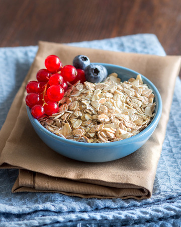 rolled oats: Rolled oats in a blue bowl with berries