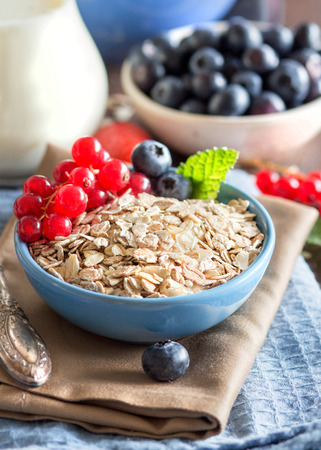 rolled oats: Rolled oats in a blue bowl on a napkin with berries and spoon