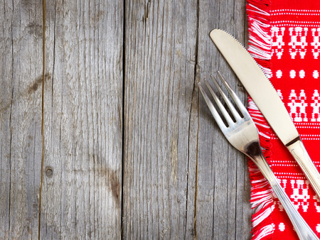 Fork and knife on kitchen towel and old wooden table photo