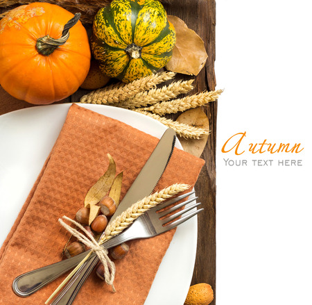 Autumn table setting with nuts, pumpkins and wheat