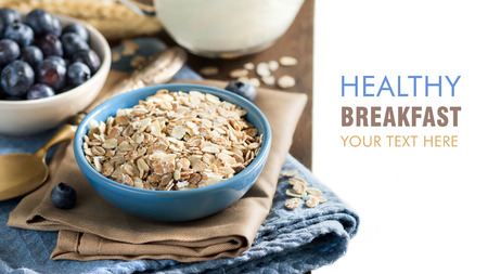 rolled oats: Rolled oats in a blue bowl on a napkin with blueberries, milk and spoon