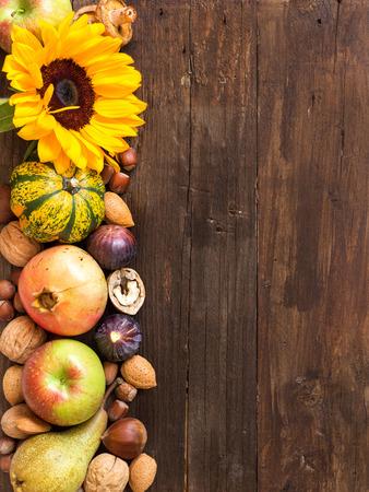 Autunno confine fatta di frutta, verdura, funghi, noci e semi di girasole su un tavolo di legno