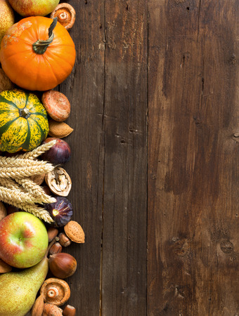 Autumn border made of fruits, vegetables, mushrooms, nuts and sunflower on a wooden table photo