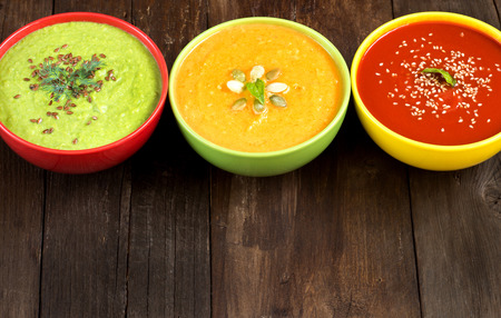 Tomatoe, pumpkin and green peas soups on a wooden table