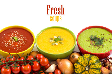 Three fresh soups in colorful bowls and vegetables Archivio Fotografico
