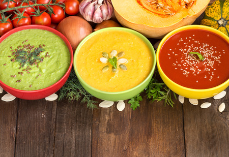 Three fresh soups in colorful bowls and vegetables on a wooden table Archivio Fotografico