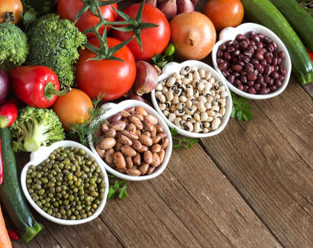 Legumes in bowls and vegetables on a wooden table photo