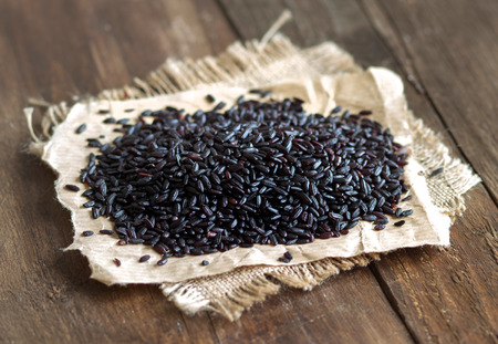 black rice: Black rice on a wooden table close up