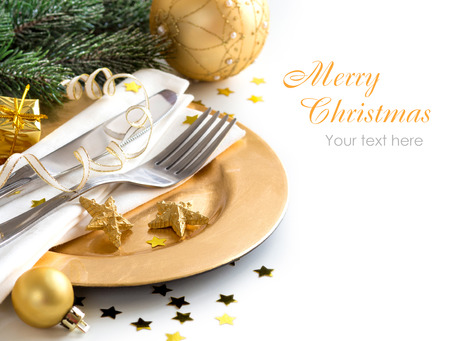 Festive table setting with golden bauble and plate Imagens