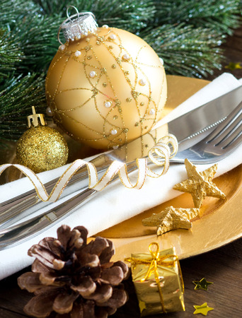 Festive table setting with golden bauble and plate photo