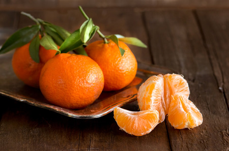 mandarin orange: Fresh Tangerines with green leaves on a wooden background