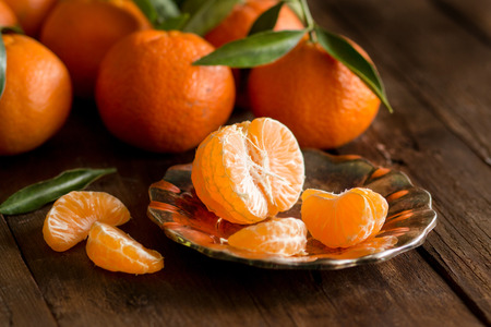 sweet foods: Fresh Tangerines with green leaves on a wooden background