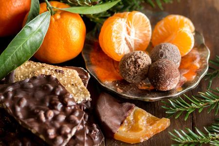 cioccolato natale: Cioccolato, tartufi e tangerins con abete su un tavolo di legno Archivio Fotografico