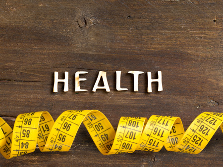 The word of Health on wood and measuring type on wooden background