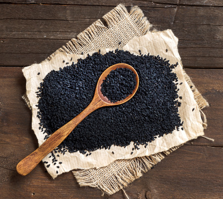 Nigella sativa or Black cumin with a spoon in wood