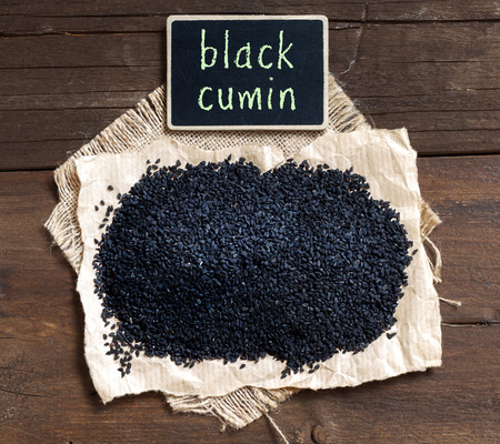 Plie of Nigella sativa or Black cumin on a wooden table