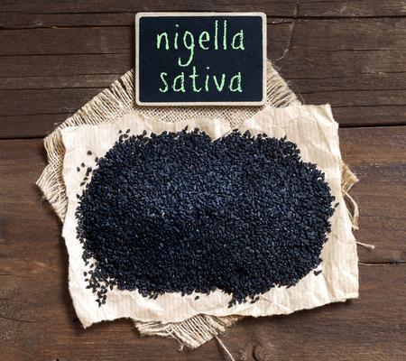 Plie of Nigella sativa or Black cumin on a wooden table