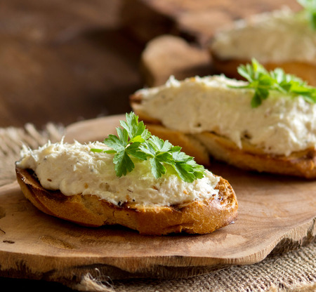 Toasted bread with a salted codfish mousse on wooden cutting board