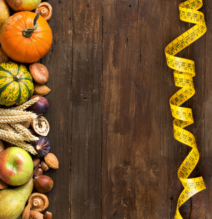 autumn food: Autumn border made of fruits, vegetables, mushrooms, nuts and sunflower on a wooden table Stock Photo
