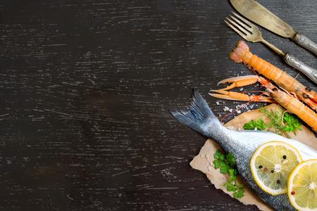 Fresh dorado fish and seafood on a dark vintage board