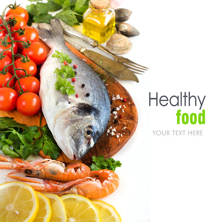 Fresh dorado fish, seafood and vegetables on a white background