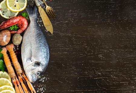 dorado fish: Fresh dorado fish, seafood and vegetables on a dark background Stock Photo